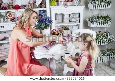 mother pouring tea into cup of her little daughter at provence style kitchen - stock photo