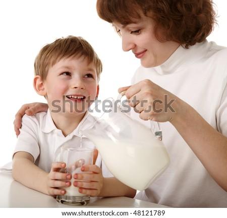 Mother pours milk to son - stock photo