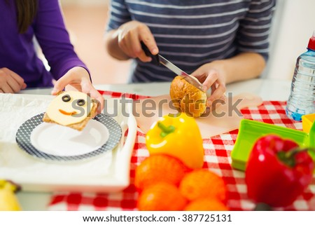 Mother preparing healthy and tasty lunch box for child at home - stock photo