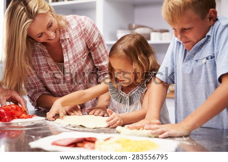 Mother preparing pizza with kids - stock photo