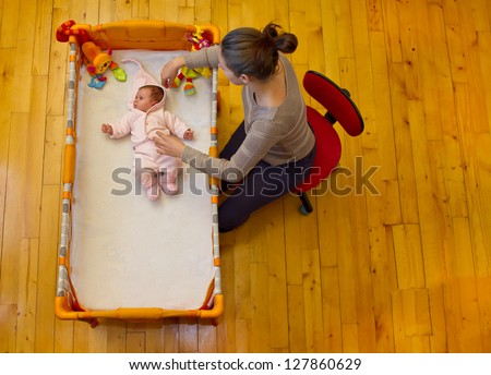 mother preparing to stroke her baby sitting next to it near her bed - stock photo