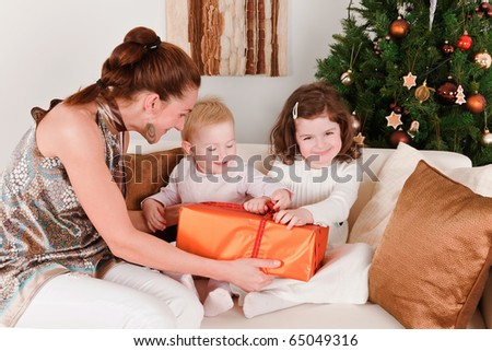 Mother present Christmas-box to her daughters - stock photo