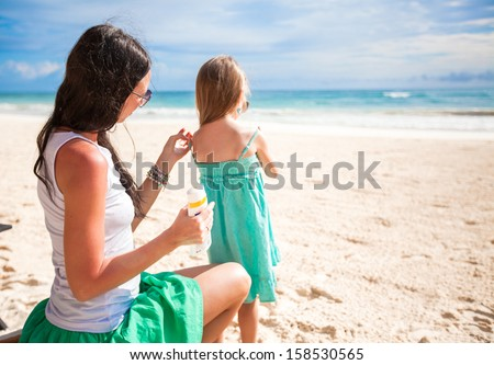 Mother protects her baby from the sun with suncream - stock photo