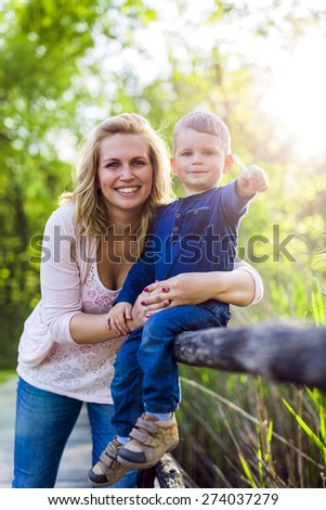 Mother proudly holding her son and smiling outdoors - stock photo