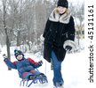 Mother pulling son on sledge, bright and white winter scene - stock photo