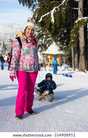 Mother pulls a sled with her son on the slopes in winter