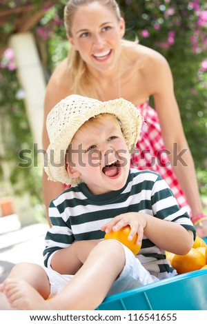 Mother Pushing Son In Wheelbarrow Filled With Oranges - stock photo