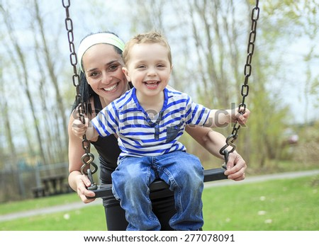 mother pushing son on swing  - stock photo