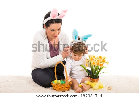 Mother put bunny ears to her son and prepare a Easter basket  - stock photo