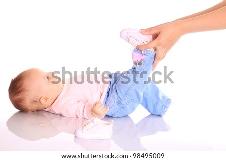 Mother putting shoes on baby leg - stock photo