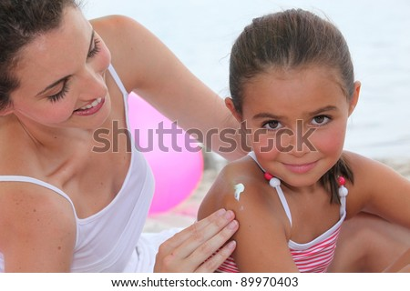 Mother putting suncream on her daughter. - stock photo