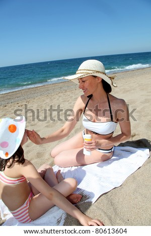 Mother putting sunscreen on her daughter's face - stock photo