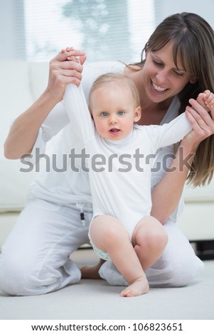 Mother raising arms of her baby in living room