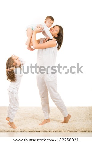Mother raising her toddler son while her daughter jumping on carpet in their house - stock photo