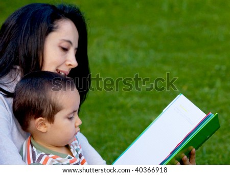 Mother reading a book to her son outdoors