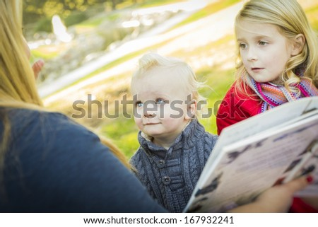 Mother Reading a Book to Her Two Adorable Blonde Children Wearing Winter Coats Outdoors.  - stock photo