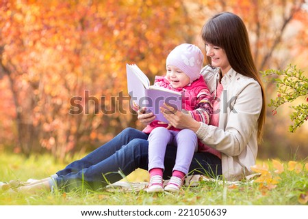mother reading a book to kid outdoors in fall - stock photo