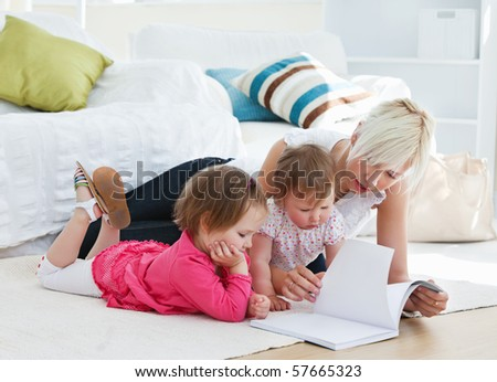 Mother reading a book with children on sofa - stock photo
