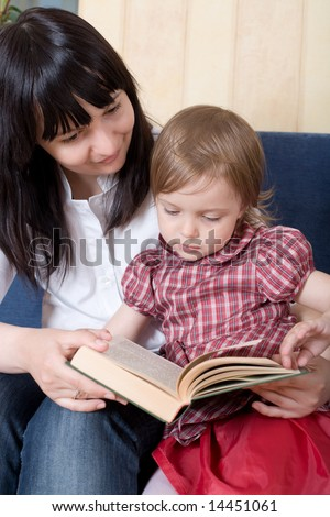 Mother reading a book with her little daughter on sofa at home