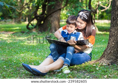 Mother reading a book with her son in park under the tree - stock photo