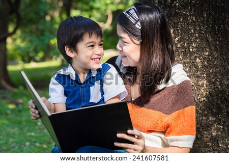 Mother reading a book with her son with smile face in park under the tree - stock photo