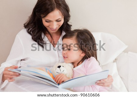 Mother reading a story to her daughter in a bedroom - stock photo