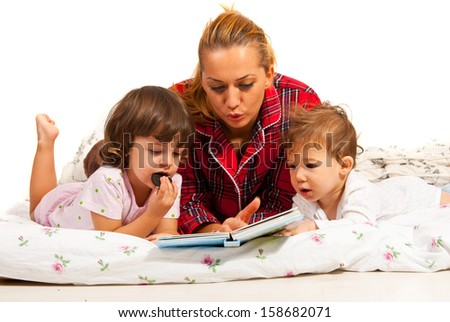 Mother reading bedtime story to her  children  in bed