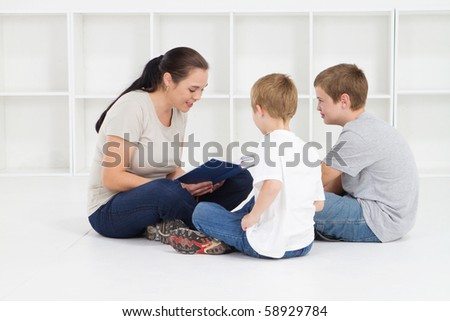 mother reading books to her kids - stock photo