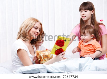 Mother reading greeting card her children presented - stock photo