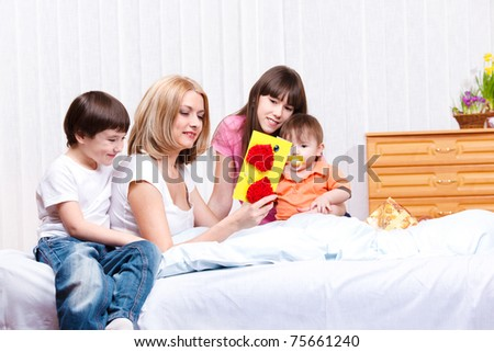 Mother reading greeting card made by children - stock photo