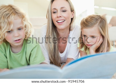 Mother reading magazine together with her children - stock photo