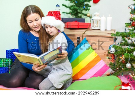 Mother reading the book daughter at the night before the Christmas - stock photo