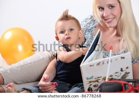 Mother reading to toddler - stock photo