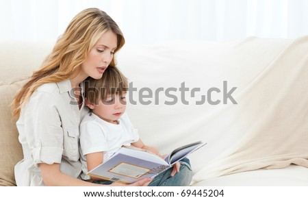 Mother reading with her son on the sofa - stock photo
