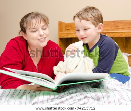 Mother reads bedtime story to young boy in his room at night - stock photo