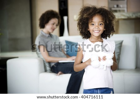 Mother reads while young daughter plays with her stuffed toy