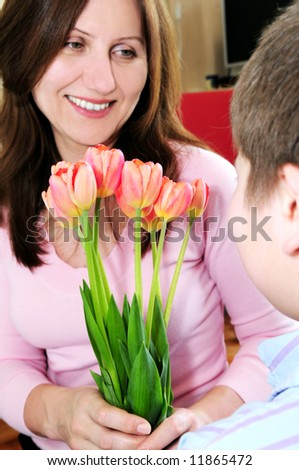 Mother receiving a bouquet of flowers from her son - stock photo
