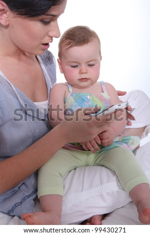 Mother resting baby on knee whilst looking at mobile telephone - stock photo