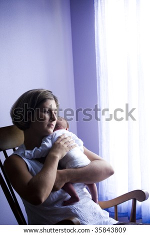 Mother rocking newborn baby in rocking chair next to window - stock photo