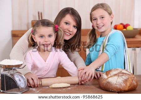 Mother rolling dough with two daughters