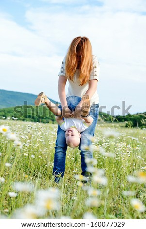 mother rolling her son in field