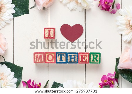 Mother's day concept - beautiful flowers with wooden blocks spelling I LOVE MOTHER. Top view. - stock photo