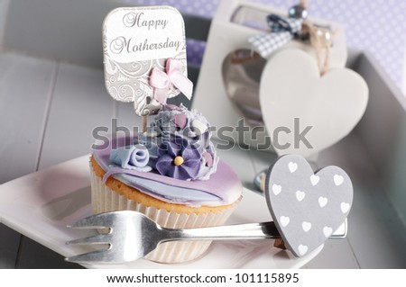 Mother's day cupcake with flower and hearts - stock photo