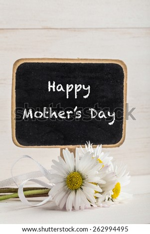 mother's day greeting with blackboard and daisies on wooden surface - stock photo