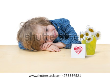 Mother's day greetings. Adorable little boy with blonde hair, blue eyes, smiling, with daisy bouquet and a red heart card on the table edge isolated over white background  - stock photo