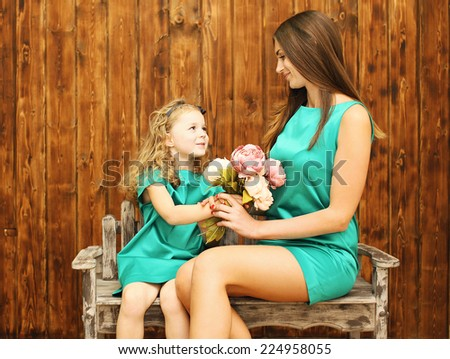 Mother's day, holiday, christmas, birthday concept - beautiful mother and daughter, little girl gives bouquet flowers mother - stock photo