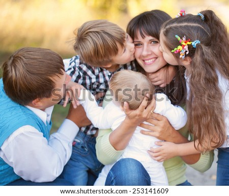 Mother's Day. Large family hugging and having fun outdoors. Selective focus on mother's hands and the head of the baby. Son and daughter kissing mother.  - stock photo