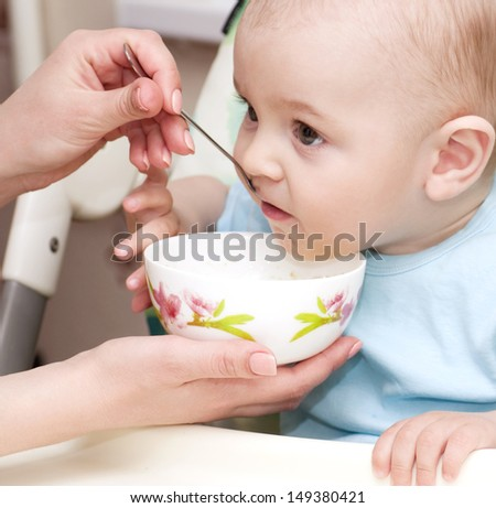 Mother's hand feeding baby boy  - stock photo
