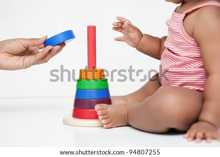 Mother's hand giving baby a piece of a wooden building toy
