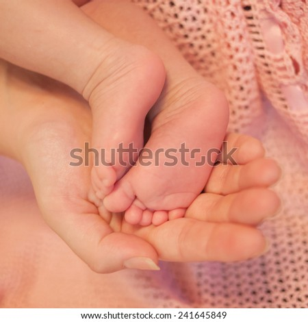 Mother's hand hold tiny feet of her newborn baby - stock photo